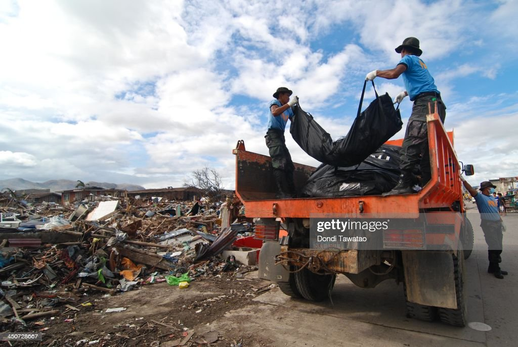 Police retrieval personnel carry bodies in a truck on November 20 2013 in Tacloban Leyte Philippines Typhoon Haiyan which ripped through the...