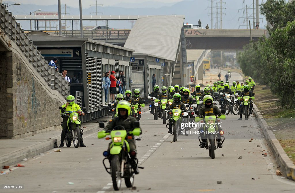 Police ride their motorcycles during a protest at the 'Transmilenio' station in southern Bogota, Colombia, on February 12, 2016. Users of public transportation blocked roads to protest what they consider poor service and high cost. Amid the protest several buses were damaged as well as stations destroyed and several demonstrators were detained by police after clashes. AFP PHOTO / GUILLERMO LEGARIA / AFP / GUILLERMO LEGARIA