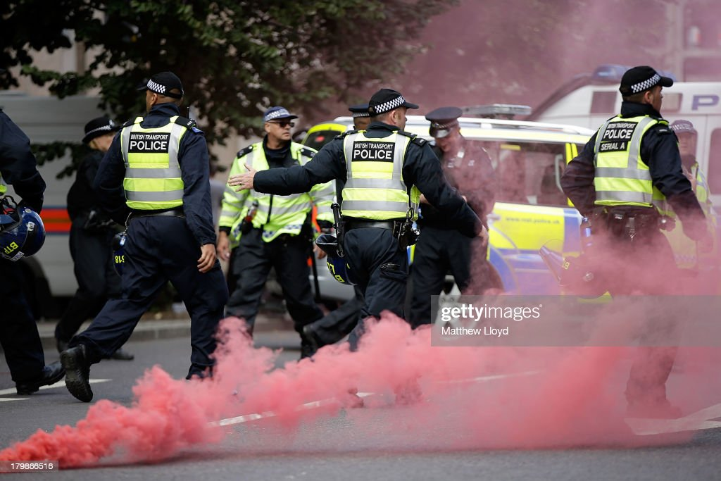 Police run after anti-fascist protestors who have thrown a smoke bomb at members of the English Defence League during a confrontation at Tower Bridge on September 7, 2013 in London, England. The EDL far-right organisation have had restrictions placed on the march by the Metropolitan police due to the fear of 'serious public disorder', but it will still proceed to the edge of Tower Hamlets, which is home to a large population of ethnic minorities.