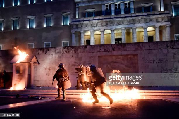 TOPSHOT Police run after protesters in front of the Greek parliament in Athens on May 18 during a demonstration on the sidelines of a voting on new...