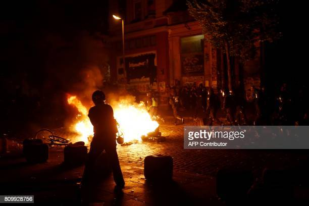 Police run past a burning pile of bins in front of the Rote Flora leftwing centre after the 'Welcome to Hell' rally against the G20 summit in Hamburg...