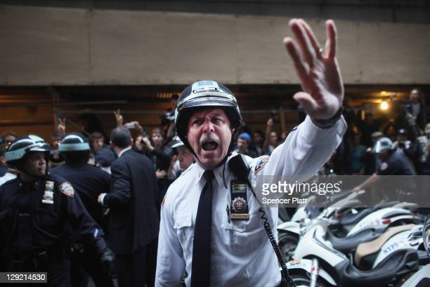 Police scuffle with members of the 'Occupy Wall Street' movement as they march through the streets of the financial district after the deadline for...