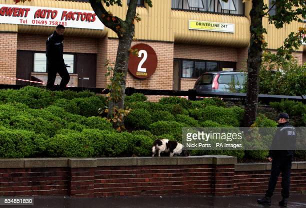 Police search an area with a sniffer dog near Driverline 247 on New Road at New Inn Pontypool South Wales