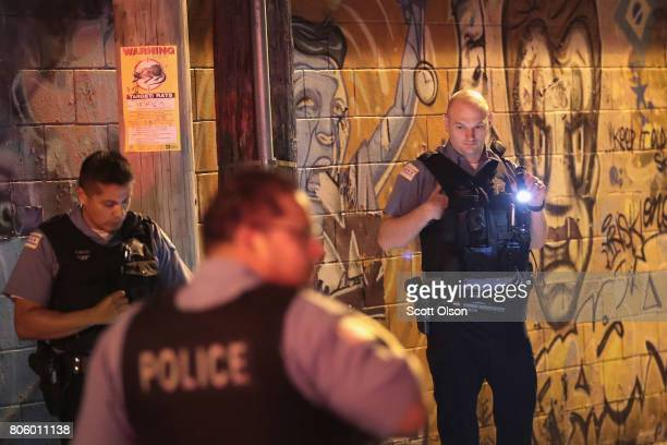 Police search for evidence after a man was shot in the Little Village neighborhood on July 2 2017 in Chicago Illinois Five people were killed and...