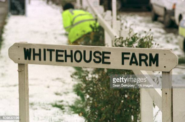 Police search the area behind the nameplate of Whitehouse Farm on whose land a Range Rover car was found with three bodies inside by the farmer The...