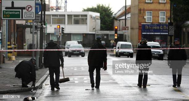 Police search the area outside the Swan pub in Tottenham north London after a 19yearold woman was shot during a fight at the bar in the early hours...
