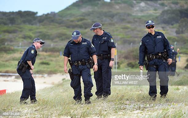 Police search the sand dunes after children playing at a Sydney beach on November 30 stumbled across the body of a baby buried under the sand...