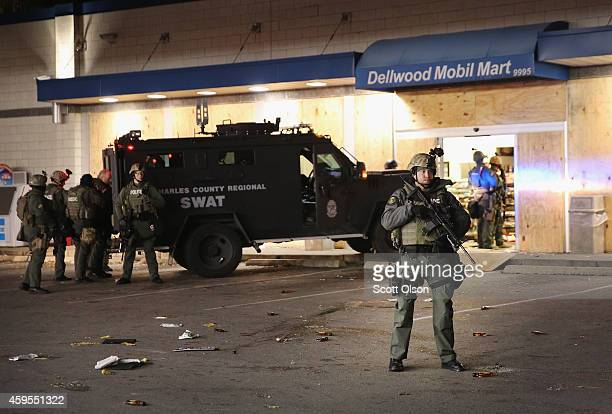 Police secure a gas station that was being ransacked by looters during rioting which broke out following the grand jury announcement in the Michael...