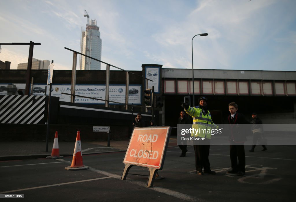 Police secure the area after a helicopter reportedly collided with a crane attached to St Georges Wharf Tower in Vauxhall, on January 16, 2013 in London, England. According to reports, the helicopter hit the crane before plunging into the road below during the morning rush hour. Two people died and nine casualties have been confirmed with one in a critical condition.