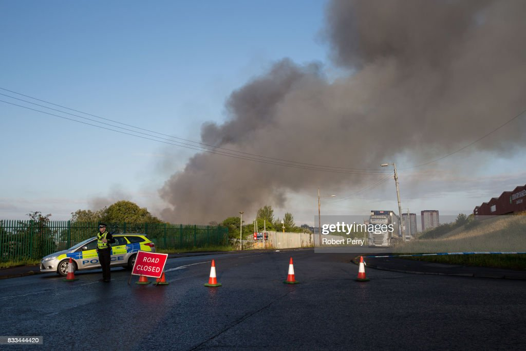 Police secure the scene of a blaze at Blochairn Fruitmarket on August 17, 2017 in Glasgow. The Scottish Fire and Rescue Service (SFRS) are tackling a fire at a warehouse the Blochairn Fruit Market. The fire began at 3.44am and residents have reported hearing two loud explosions. There are no reported casualties or injuries but the SFRS are struggling to get the blaze under control due to low water pressure.