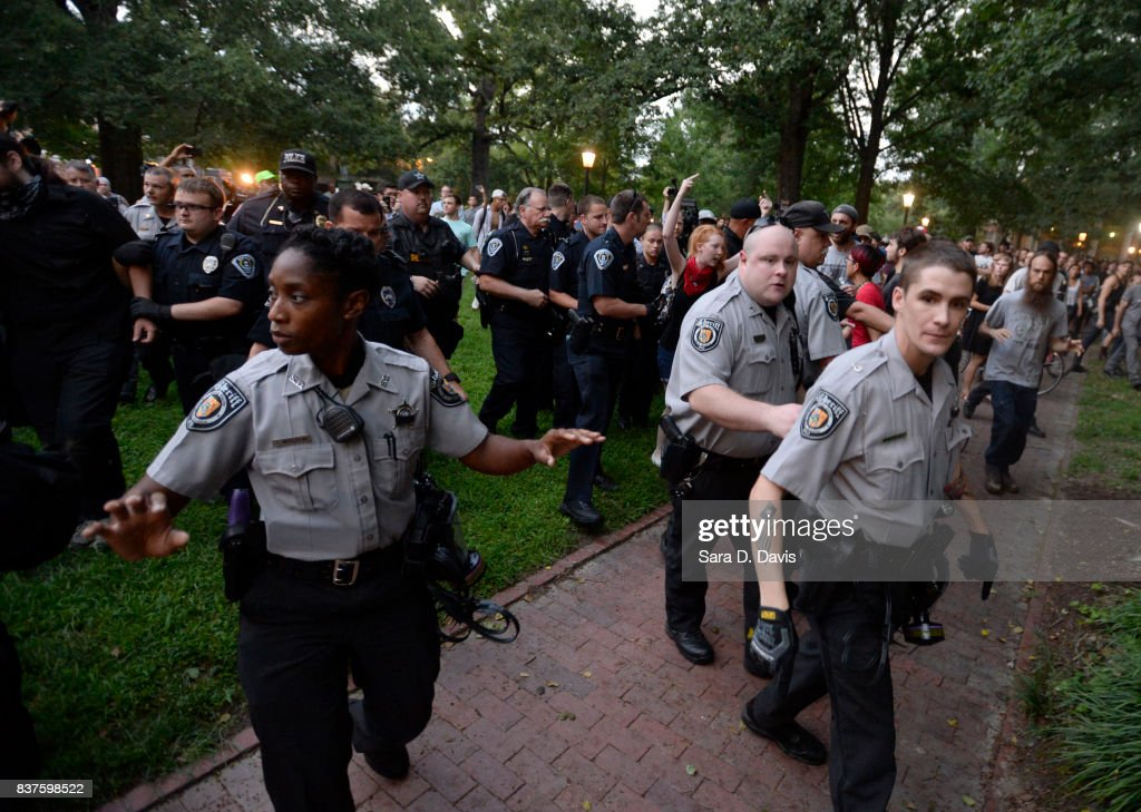 Police shove demonstrators back to allow an arrested man through during a rally for the removal of a Confederate statue coined Silent Sam on the campus of the University of Chapel Hill on August 22, 2017 in Chapel Hill North Carolina.
