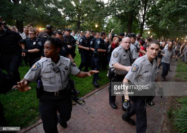 Police shove demonstrators back to allow an arrested man through during a rally for the removal of a Confederate statue coined Silent Sam on the...