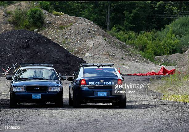 Police sit at the crime scene where a body was discovered on Monday near the home of New England Patriots player Aaron Hernandez in North...