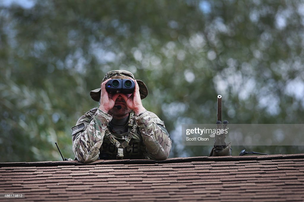 A police sniper keeps watch from the roof of a home while other police search nearby for suspects involved in the shooting of an officer September 1...