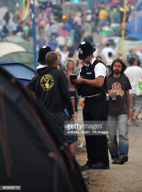 Police speak to a festival goer during the 2009 Glastonbury Festival at Worthy Farm in Pilton Somerset