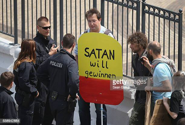 Police speak to a protester who is holding a sign that reads 'Satan wants to win' outside the venue of the 2016 Bilderberg Group conference on June 9...