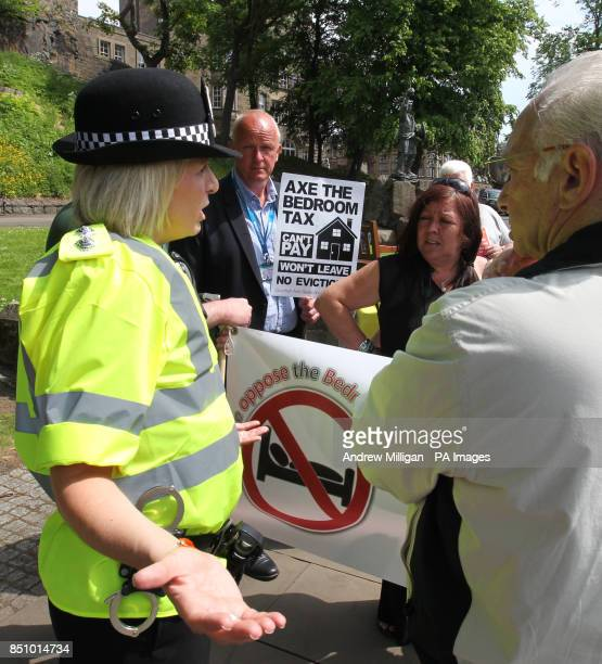 Police speak to protesters after Alan Smart was taken away by police after performing on his guitar with the anti bedroom tax protesters outside the...