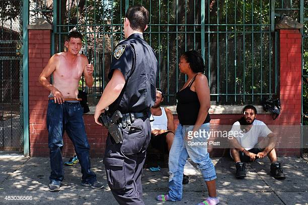 Police speak with men fighting who are high on K2 or 'Spice' a synthetic marijuana drug along a street in East Harlem on August 5 2015 in New York...