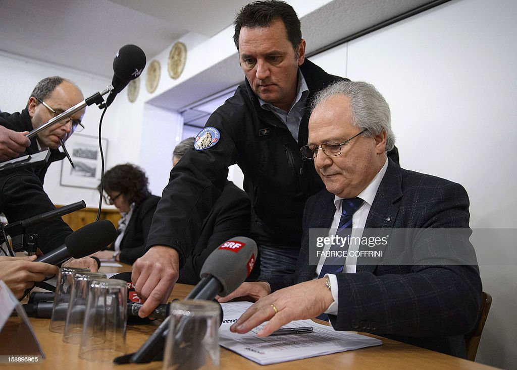 Police spokesman Jean-Marie Bornet (L) helps the head of the police Robert Steiner (R) during a press conference on January 3, 2013 in Daillon. A gunman has opened fire in a village in southern Switzerland, killing three people and wounding two others.