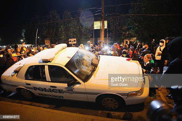 A police squad car is turned over by demonstrators during a protest on November 25 2014 in Ferguson Missouri Yesterday protesting turned into rioting...