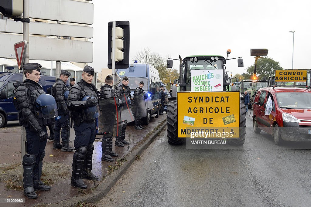 Police stand as farmers block the road with tractors in Trappes, near Paris, on November 21, 2013 to slow traffic during an 'operation escargot' (snail operation) called by the Ile-de-France farmers' union FDSEA to protest against higher tax rates and excess of regulations. The French government on November 21 ordered irate farmers blocking roads into Paris to halt their protest over tax hikes after accidents that left one person dead and six injured.