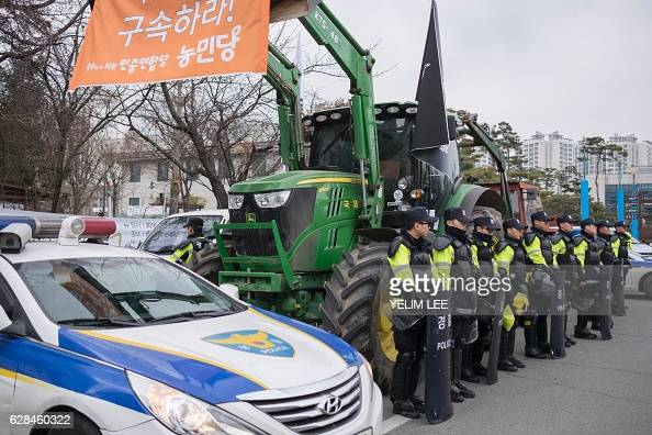 Police stand before tractors and farmers from Gyeonggi and Chungcheong province as they make their way to Seoul to protest against the ongoing...