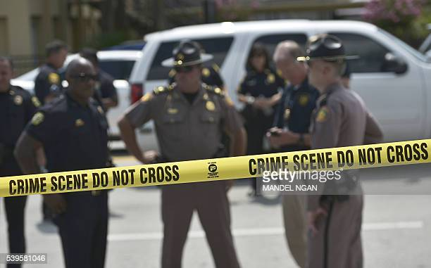TOPSHOT Police stand behind a crime scene tape near the mass shooting at the Pulse nightclub on in Orlando Florida on June 12 2016 A somber President...