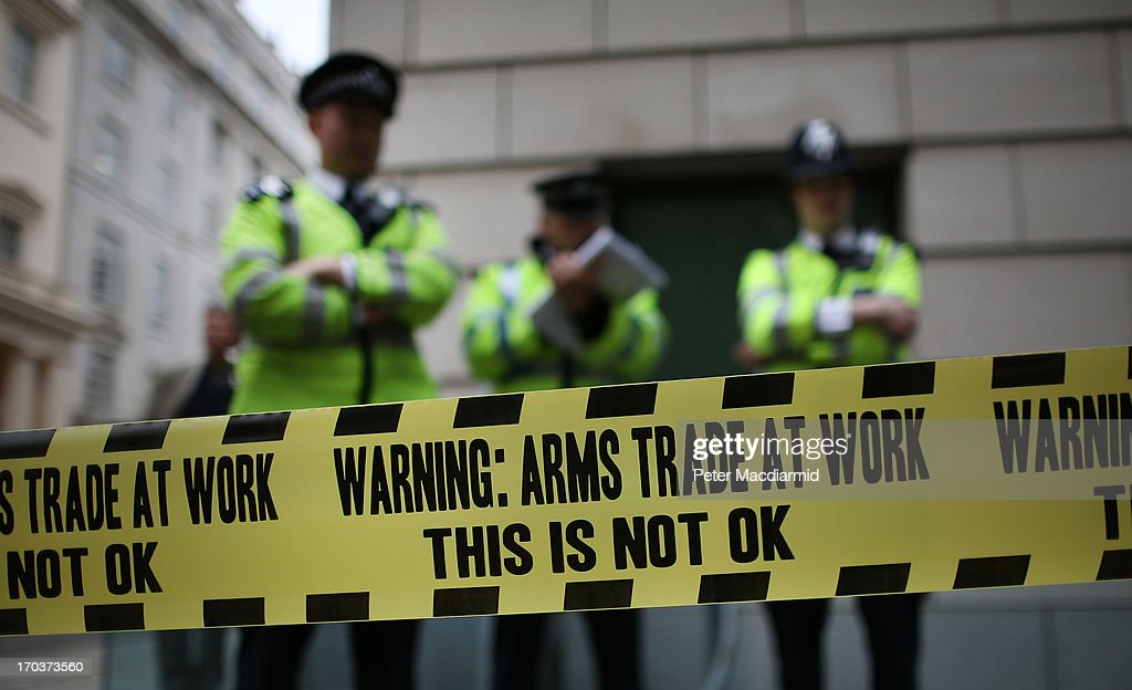 Police stand behind some anti-arms trade cordon tape during protests outside arms manufacturer BAe Systems on June 12, 2013 in London, England. Protests are expected to take place in London in the lead up to the G8 meeting to be held in Enniskillen, Northern Ireland on the 17 and 18 June 2013. The chosen location is only 8 kilometers from the scene of one of Northern Ireland's worst killings back in 1987, however Cameron is confident that it's secluded location will deter any potential trouble.