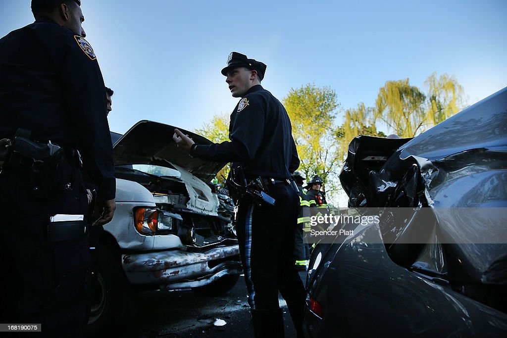 Police stand beside damaged vehicles after a multi-car accident on May 6, 2013 in the Brooklyn borough of New York City. It was reported that seven people were aided in the early evening pile-up, which occurred on the Prospect Expressway.