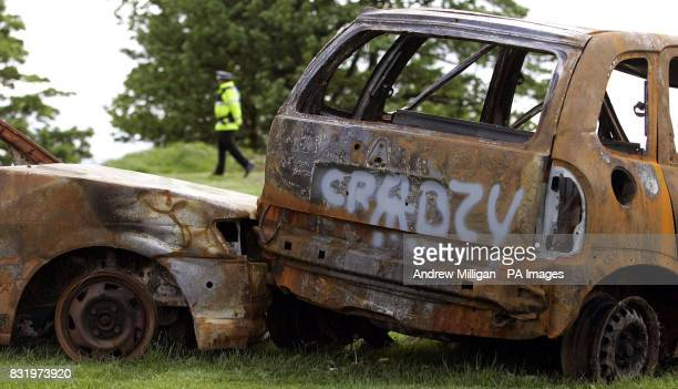 Police stand by a burnt out vehicle as they await the arrival of the Prince of Wales and the Duchess of Cornwall who will see how a Prince's Trust...