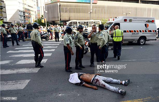 Police stand by a man murdered in one of the main streets of Caracas on May 2012 In Caracas the capital of the South American country with the...
