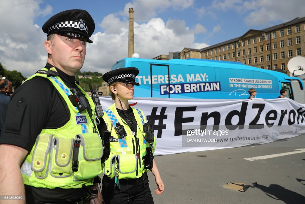 Police stand by as protesters unfurl a large banner against zero hours contracts in front of the Conservative Party 'battle bus' outside the venue where Prime Minister Theresa May and government ministers will launch the Conservative Party general election manifesto in Halifax in northern England on May 18, 2017. British Prime Minister Theresa May will on May 18 promise to crack down on immigration from outside the European Union as she unveils the Conservative Party's manifesto. / AFP PHOTO / POOL / Dan Kitwood