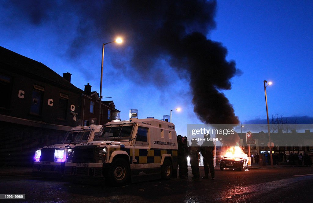 Police stand by their armoured vehicles as a car burns following violence between, loyalists, nationalists and the police in east Belfast, Northern Ireland on January 12, 2013 after the latest loyalist march against the decision to limit the days on which the Union Flag would be flown over Belfast City Hall. Northern Irish demonstrators loyal to Britain clashed with nationalists and police on Saturday in fresh protests against curbs on flying the British flag, leaving four officers injured, police said. The clashes were the latest to blight the British province after more than five weeks of violent disorder over the flag issue.