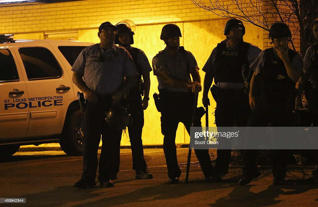 Police stand guard along Florissant Avenue to prevent a repeat of the unrest that followed the recent death of Michael Brown on August 21, 2014 in Ferguson, Missouri. Brown was shot and killed by a Ferguson police officer on August 9. Despite the Brown family's continued call for peaceful demonstrations, violent protests have erupted nearly every night in Ferguson since his death.