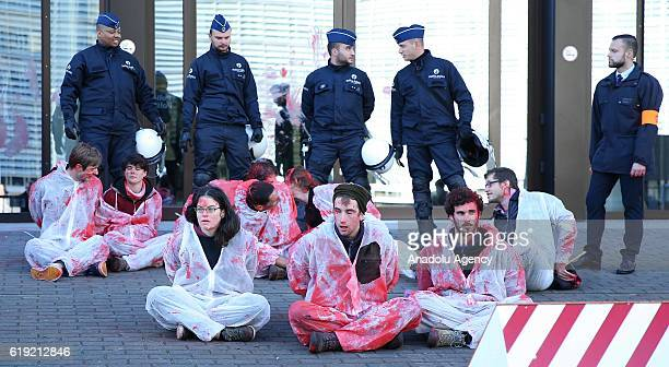 Police stand guard as activists wearing suits covered in fake blood take part in protests against the Comprehensive Economic and Trade Agreement a...
