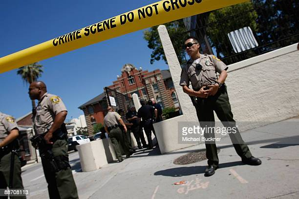 Police stand guard as Craig Harvey of the Los Angeles County coroner's office holds a press conference to announce that the autopsy on singer Michael...