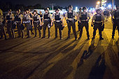 Police stand guard as demonstrators marking the oneyear anniversary of the shooting of Michael Brown protest along West Florrisant Street on August...
