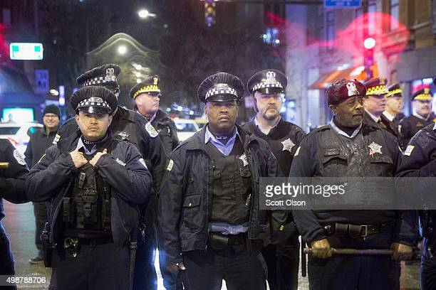 Police stand guard as demonstrators protest the death of Laquan McDonald on November 25 2015 in Chicago Illinois Small and mostly peaceful protests...