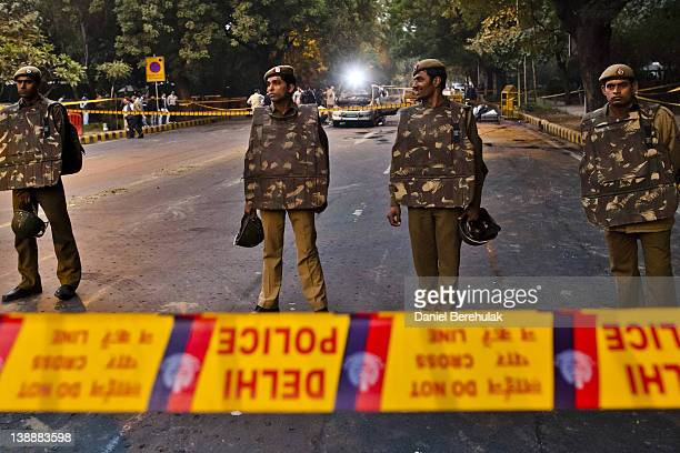 Police stand guard as forensics officers examine a damaged Israeli embassy vehicle after an explosion on February 13 2012 in New Delhi India A minor...