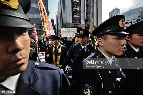 Police stand guard as hundreds of people stage a protest to express their opposition to a racist demonstration which was held at the Korean area in...