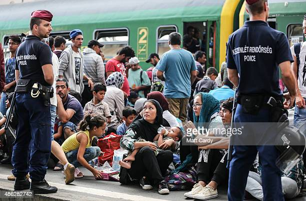 Police stand guard as migrants sit on the platform of Keleti station after it was reopened this morning in central Budapest on September 3 2015 in...