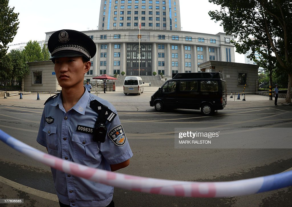 Police stand guard as officials arrive for the trial of disgraced politician Bo Xilai on the fourth day of Bo's trial at the Intermediate People's Court in Jinan, Shandong Province on August 25, 2013. Once one of China's highest-flying politicians, Bo Xilai found himself in the criminal dock on trial for bribery and abuse of power in the country's highest-profile prosecution in decades. His downfall began when a British businessman was found dead in a hilltop hotel room. As the drama finally nears its conclusion, the Communist Party is touting it as proof of its intent to crack down on corruption. AFP PHOTO/Mark RALSTON