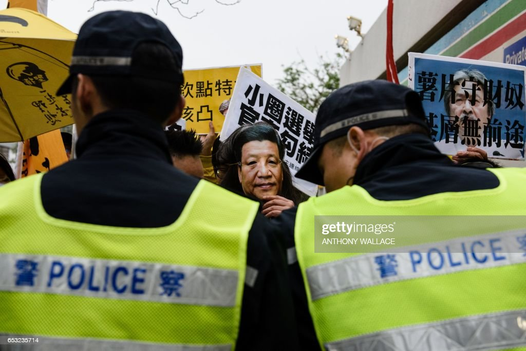 Police stand guard as pro-democracy lawmaker Leung Kwok-hung (C) wears a mask depicting Chinese President Xi Jinping as he joins protesters outside a studio before Hong Kong's three leadership candidates John Tsang, Carrie Lam and ex-judge Woo Kwok-hing face off in their first televised debate in Hong Kong on March 14, 2017. Hong Kong's three leadership candidates faced off in their first televised debate on March 14 as criticism mounts over a voting process which favours Beijing and bypasses the majority of the electorate. / AFP PHOTO / Anthony WALLACE