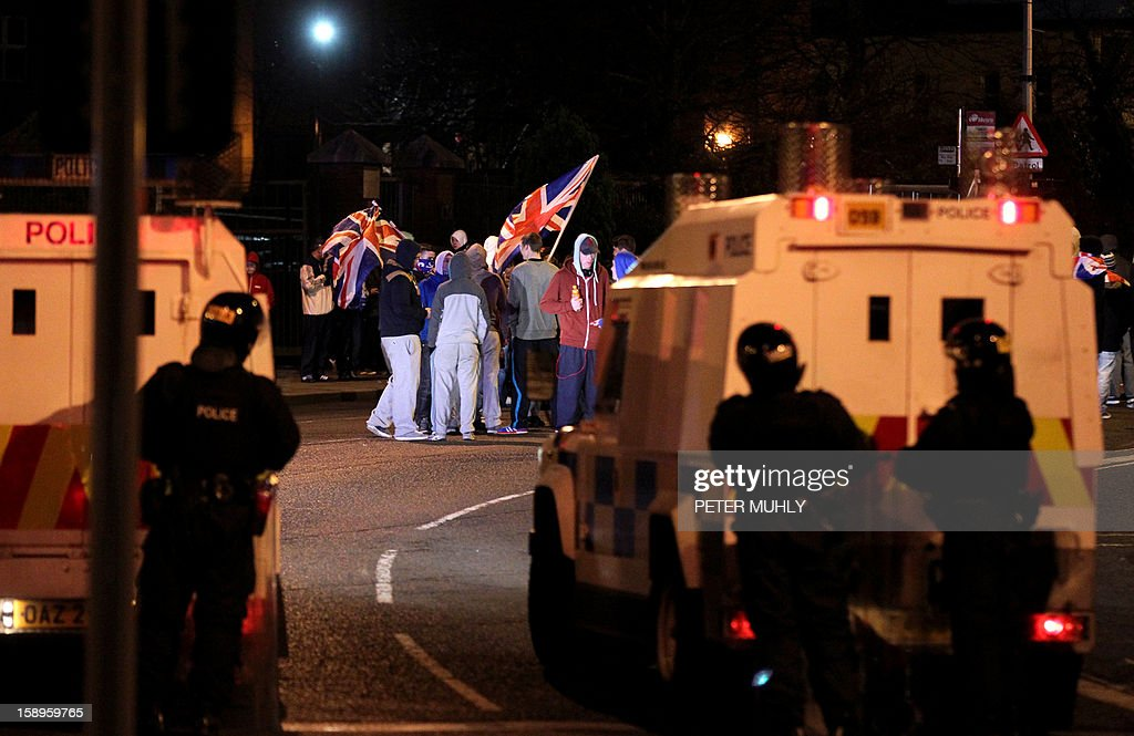 Police stand guard as protesters wave the Union flag during clashes in Belfast, Northern Ireland, on January 4, 2013. Tensions have risen in the British province since councillors voted on December 3, 2012 to limit the number of days the Union flag can fly over the City Hall to 17, outraging loyalists who believe Northern Ireland should retain strong links to Britain. AFP PHOTO/ PETER MUHLY