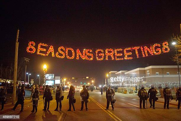 Police stand guard as protests engulf Ferguson on November 26 2014 in Ferguson Missouri Over 2000 Missouri national guardsmen are being deployed a...