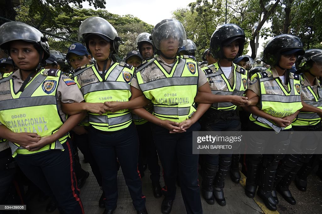 Police stand guard as public university students in Venezuela protest the policies of the government of President Nicolas Maduro in Caracas on May 26, 2016. / AFP / JUAN