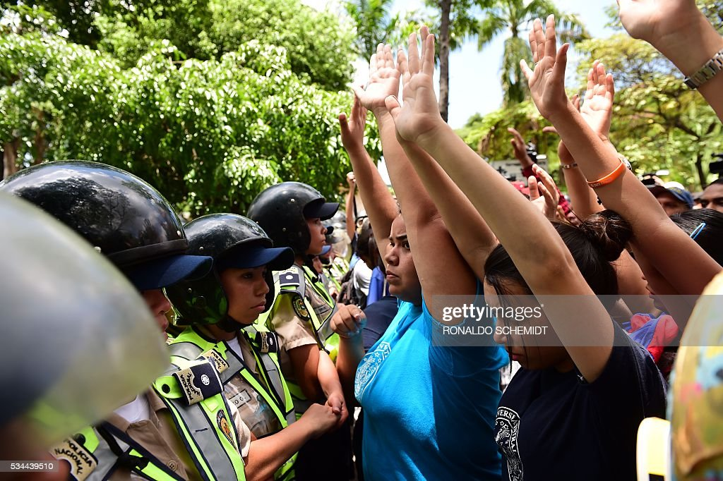 Police stand guard as public university students in Venezuela protest the policies of the government of President Nicolas Maduro in Caracas on May 26, 2016. / AFP / RONALDO