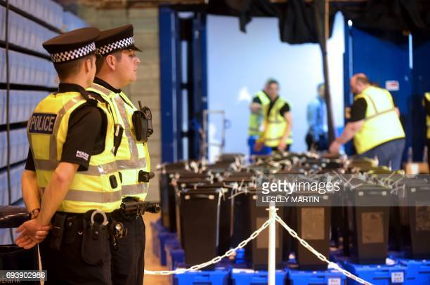 TOPSHOT Police stand guard as the ballot boxes arrive at the Meadowbank Sports Centre counting centre in Edinburgh Scotland on June 8 after the polls...