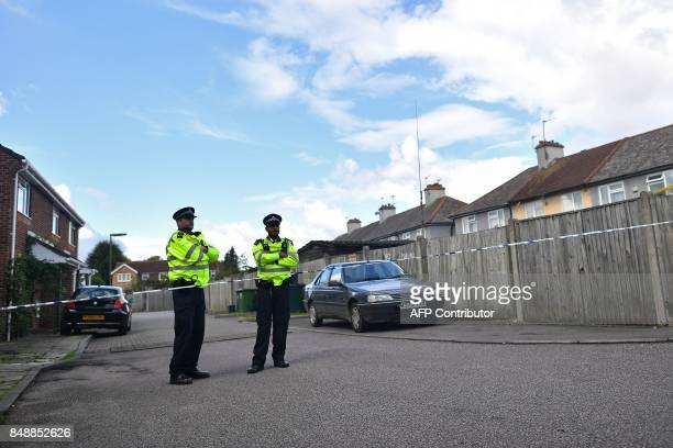 Police stand guard at a police cordon near to the rear of a house in Sunbury west of London on September 18 as they continue investigations into the...