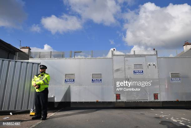 Police stand guard at a police cordon outside a house in Sunbury west of London on September 18 as they continue investigations in to the September...